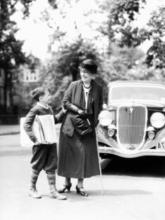 h-armstrong-roberts-newsboy-with-stack-of-papers-under-arms-helping-elderly-woman-with-cane-cross-street